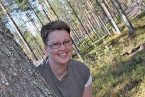 Lyhythiuksinen silmälasipäinen nainen kurkistaa männyn rungon takaa metsässä