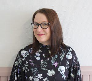 Tummatukkainen, silmälasipäinen nainen värikkäässä puserossa