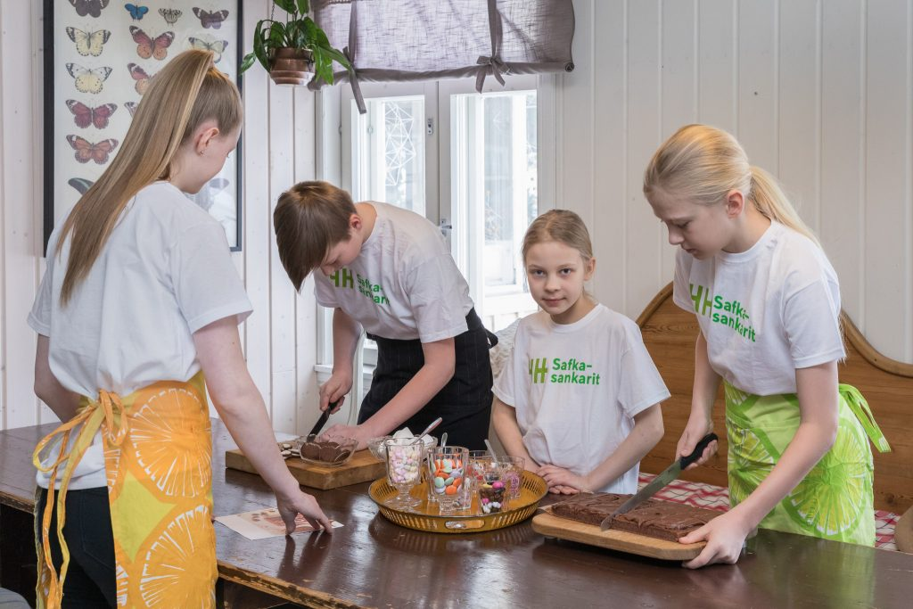 Neljä lasta ruokapöydän äärellä laittamassa ruokaa