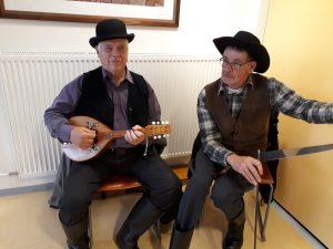 kuvassa mandoliinia ja sahaa soittavat miehet, jotka ovat sonnustautuneet vanhanaikaisiin saappaisiin, liiveihin ja hattuihin.