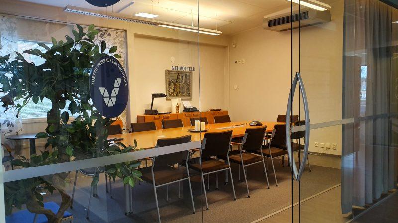 Kokoustilakuva, jossa näkyy tuoleja ja pitkä pöytä kera viherkasvien