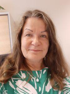Pitkähiuksinen nainen vihreävalkoisessa paidassa